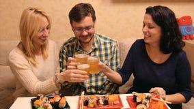 HD het bedrijf drinkt bier en eet sushi in een koffie stock videobeelden