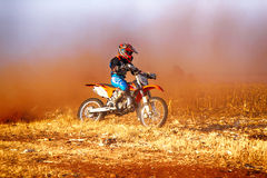 HD - Junior Motorbike kicking up trail of dust on sand track dur Stock Image