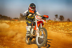 HD - Junior Motorbike kicking up trail of dust on sand track dur Royalty Free Stock Photos