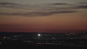 HD lengte van een jet die in silhouet tegen een oranje zonsondergang landen stock footage
