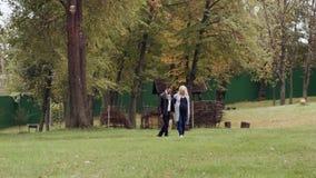 HD marchant dans un couple de parc tenant des mains, femme enceinte avec le ventre de bébé clips vidéos
