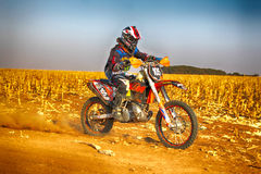 HD - Motorbike kicking up trail of dust on sand track during ral Royalty Free Stock Images