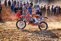 HD - Motorbike kicking up trail of dust on sand track during ral Stock Photo