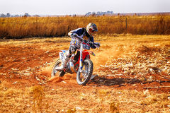 HD - Motorbike kicking up trail of dust on sand track during ral Royalty Free Stock Photography