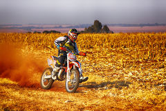 HD - Motorbike kicking up trail of dust on sand track during ral Stock Image