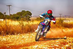 HD - Motorbike kicking up trail of dust on sand track during ral Stock Photography