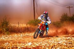 HD - Motorbike kicking up trail of dust on sand track during ral Royalty Free Stock Photo