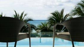 HD pieno Zummi della sedia di rilassamento di vacanza due davanti alla piscina vicino alla spiaggia con la vista dell'albero e de archivi video