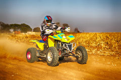 HD- Quad Bike kicking up trail of dust on sand track during rall Stock Images