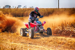 HD- Quad Bike kicking up trail of dust on sand track during rall Royalty Free Stock Photo