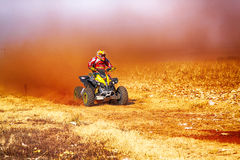 HD- Quad Bike kicking up trail of dust on sand track during rall Stock Photos