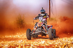HD- Quad Bike kicking up trail of dust on sand track during rall Royalty Free Stock Image