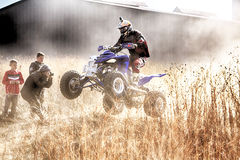 HD- Quad Bike ramping in dust on sand track during rally race. Royalty Free Stock Photography