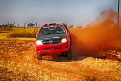 HD RED truck kicking up dust on turn ar rally Royalty Free Stock Images