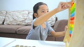 HD stänger sig upp den asiatiska lilla flickan för skottet som spelar kulrammet arkivfilmer