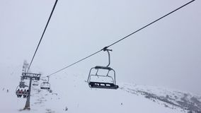 1080 HD hyper lapse video clip of four person ski chair lift on a misty mountain. 1080 HD time lapse hyper lapse video clip of four person ski chair lift on a stock video