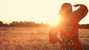 African Woman in Traditional Clothes Standing in Farm Field at Sunset or Sunrise. HD Video clip of African woman farmer in traditional clothes standing in a stock video