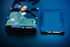HDD next to SSD. Hard disk next to ssd disk (solid state drive) blue technological background - tilt-shift lens used to accent the center of the hdd and to Stock Photo