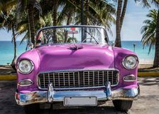 HDR古巴桃红色美国经典汽车停放了在棕榈下在海滩附近在巴拉德罗角 免版税库存照片