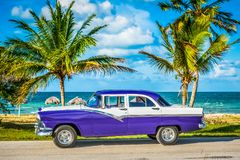 HDR -在前面侧视图的停放的美国白色蓝色葡萄酒汽车在哈瓦那古巴- Serie古巴报告文学的海滩 图库摄影