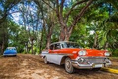 HDR -在古巴- Serie古巴报告文学的省停放的美国红色和蓝色经典汽车圣克拉拉 免版税库存照片