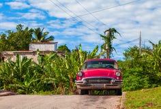 HDR -在圣克拉拉古巴- Serie古巴报告文学的小巷停放的美国红色葡萄酒汽车 库存图片