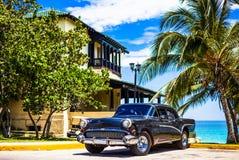 HDR -在正面图停放的美国黑葡萄酒汽车在巴拉德罗角古巴- Serie古巴报告文学的海滩前 免版税图库摄影