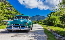 HDR -在countrystreet的蓝绿色美国葡萄酒汽车驱动在乡下从特立尼达古巴- Serie古巴报告文学 库存照片