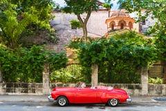 HDR -在Malecon停放的美国红色Oldsmobile敞篷车葡萄酒汽车在堡垒在哈瓦那古巴- Serie古巴的el Morro前 库存照片