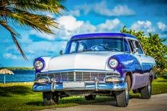 HDR -在Malecon停放的美国蓝色经典汽车在哈瓦那古巴- Serie古巴报告文学的海滩附近 库存照片