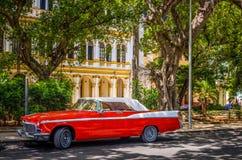 HDR -有在哈瓦那古巴- Serie古巴报告文学的小巷上停放的白色屋顶的美国红色经典汽车 免版税库存图片