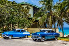 HDR -有在海滩停放的白色屋顶的美国蓝色经典汽车在巴拉德罗角古巴- Serie古巴的棕榈下 免版税库存照片