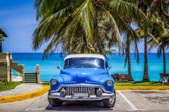 HDR -美国蓝色经典汽车停放在海滩的棕榈下在巴拉德罗角古巴- Serie古巴报告文学 免版税图库摄影