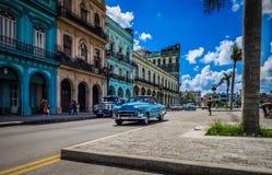 HDR -街道生活场面在有蓝色美国葡萄酒汽车的哈瓦那古巴- Serie古巴报告文学 库存照片