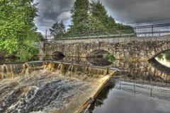 水坝和水力发电站的老石桥梁在HDR的 免版税库存图片