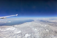 HDR Aerial photo of the landscape with clouds, snowy mountains and view stretching all the way to the horizon with airplane wing Stock Photos