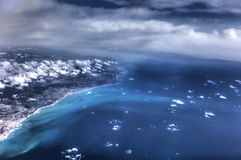HDR Aerial photo of the landscape and coastline with clouds, snowy mountains and view stretching all the way to the horizon Royalty Free Stock Photos
