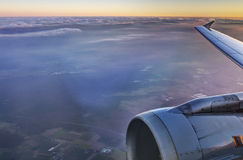HDR Aerial photo of the landscape under a cloud cover and a horizon, with an airplane wing and engine at sunset. HDR Aerial photo of the landscape under a cloud Stock Images