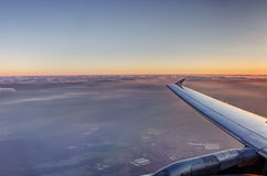 HDR Aerial photo of the landscape under a cloud cover and view stretching all the way to the horizon with an airplane at sunset Stock Image