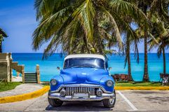 HDR - American blue classic car parked under palms on the beach in Varadero Cuba - Serie Cuba Reportage royalty free stock photography