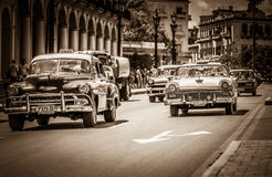 HDR - American Chevrolet classic cars and a Ford Fairlane classic car with white roof drives o. N the street in Havana Cuba - Retro SEPIA Serie Cuba Reportage Stock Image