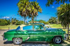 HDR - American green classic car parked under palms in Varadero Cuba - Serie Cuba Reportage.  Stock Photography