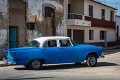 HDR american vintage car drives in a village in the countryside from Cuba Royalty Free Stock Photo