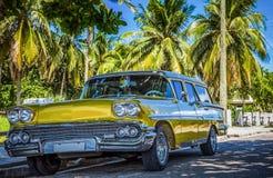 HDR - Amerykański złoty Ford Brookwood parkujący pod palmami blisko plaży w Varadero Kuba, Seria Kuba reportażu - zdjęcie stock