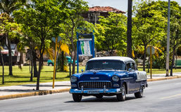 HDR blue american classic car with white roof on the street in Cubaith a latino Royalty Free Stock Photos