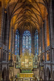 HDR cathedral hall with altar. Ancient hall of a chapel in hdr. Lonely archway is leading to the stained-glass windows. Altar with icons is in the center of the Stock Image