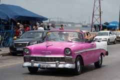 HDR Cuba pink american Oldtimer drives on the Malecon Promenade in Havana. Cuba pink american Oldtimer drives on the Malecon Promenade in Havana Royalty Free Stock Photography