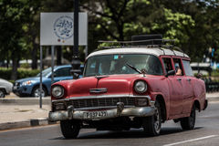 HDR Cuba red american Oldtimer drives on the promenade Malecon in Havana Stock Photo