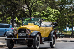 HDR Cuba yellow american Oldtimer drives on the Malecon Promenade in Havana Royalty Free Stock Images