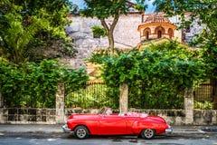 HDR - Czerwony amerykański odwracalny rocznika samochód parkujący przed dziejowym fortecą el Morro w Hawańskim Fotografia Royalty Free